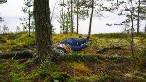 Sarah Grönstrand ligger raklång under en tall. Många knotiga rötter syns på marken.