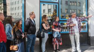 Mies osoittaa jotakin vieressään oleville ihmisille kadulla, taustalla näyteikkuna.
