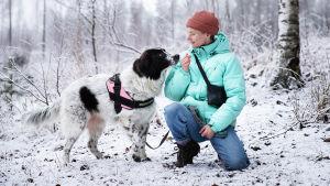 Nita koiransa kanssa metsässä.