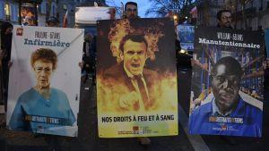 Demonstranter håller upp plakat med bilder på en brinnande president Macron under protester i Paris.