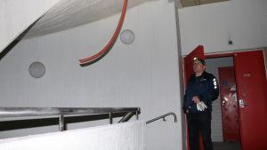 En man med lampa i pannan tittar på en röd ledning som hänger från taket.