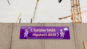 "Slussenskylt där det står ""Turister hitåt, hipsters ditåt""."