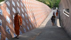 Ett minnesmärke utanför fiskebyn Ban Nam Khem som personer går igenom.