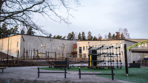 Klätterställningar, och i bakgrunden ett skolhus
