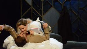 En kvinna och en man ligger på en säng på en teaterscen. Kvinnan ligger på mannen med ett häfte i handen. Mannen har en penna i handen.