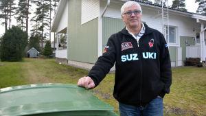 En man som står vid ett avfallskärl, i bakgrunden ett småhus.