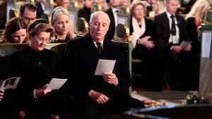 Norges kung och drottning sitter längst fram i en kyrka.
