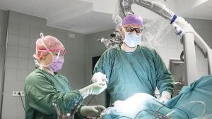 Neurokirurgi Aki Laakso poistaa Laurin aivoista pullistuman.