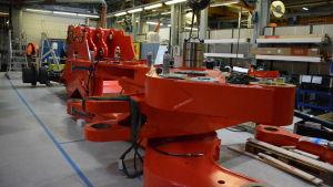 En stor röd del av en lastare ligger på golvet i en fabrik.