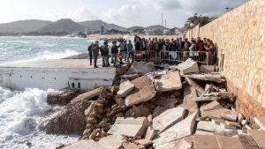 Spaniens premiärminister Pedro Sanchez tittar tillsammans med en massa andra människor på förödelsen vid stranden Cala Rajada i Mallorca.