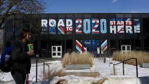 """Kvinna med kaffemugg framför en byggnad med texten """"Road to 2020 starts here""""."""