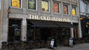 The Old Irish Pub i Danmark. Fasaden från gatan med uteservering.