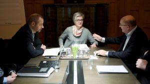 Två män i kostym och en kvinna i grå tröja sitter runt ett bord.