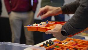 En vuxen hand plockar lego ur en låda.