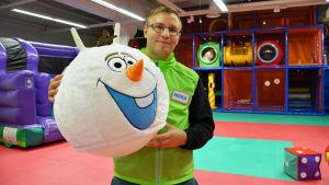 En man i grönsvart jacka står och håller i en stor rund dyna som ser ut som ett leende snögubbshuvud. Bakom mannen syns en innelekpark.