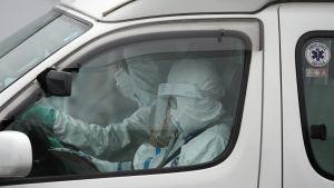 Ambulanspersonalen var klädd i full skyddsdräkt då de hämtade en smittad passagerare från Diamond Princess på söndagen.