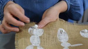 hand syr fast pärla på ett kanintryck på en duk