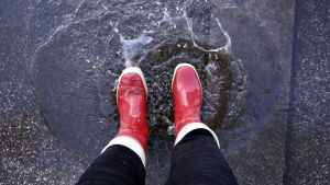 En persons fötter iklädda röda stövlar som står i en vattenpöl.