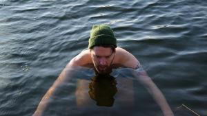 En man med mössa i havet.