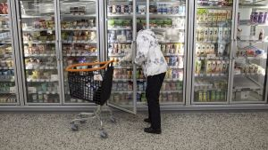 En kvinna plockar en jugurtkartong ur butikens kyldisk.