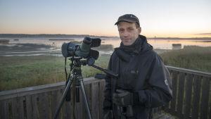 Markku Mikkola-Roos står i ett fågeltorn i gryningen.