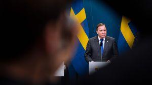 Stefan Löfven i kostym och blå slips står bakom ett podium.
