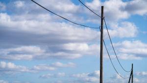 Vanhat sähkötolpat taivasta vasten maaseudulla.