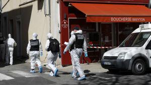 Valkoisiin suojapukuihin pukeutuneet rikospaikkatutkijat kävelevät lihakaupan ohi.