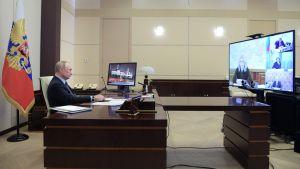 President Vladimir Putin sitter vid ett skrivbord och ser på en tv-skärm.