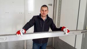 En man står och lutar händerna mot en bom.
