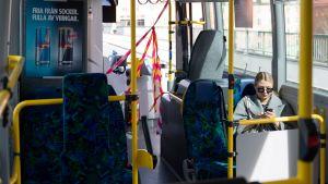Vy från buss i Stockholm med bara en passagerare och med avspärrning så passagerare inte har kontakt med chauffören.