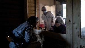 En kvinna talar med sin mor och vårdare med munskydd bakom glasruta på äldreboende i Frankrike