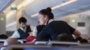 Två flygvärdar pratar med kunder i ett långdistansflyg.