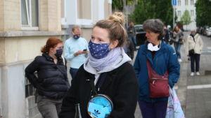 Läraren Margot köar utanför textilaffären i Bryssel. Hon ska köpa munskydd som hon behöver på jobbet.