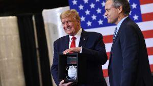 Donald Trump tar emot en ansiktsmask under sitt besök i Phoenix i delstaten Arizona.