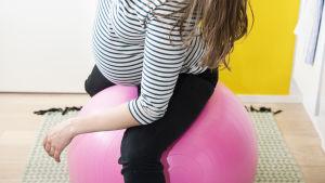 Raskaana oleva nainen venyttelee jumppapallon päällä.