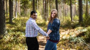 Anm Rezzakuzzaman ja Petra Ranta-Rezzakuzzaman seisovat metsäpolulla ja pitävät toisiaan kädestä kiinni.