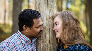 Petra Ranta-Rezzakuzzaman ja Anm Rezzakuzzaman katsovat nojaavat puunrunkoon ja katsovat toisiaan silmiin.