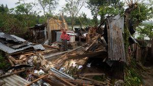 En person står mitt bland ett hus som totalförstörts i ett oväder.