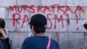 En ung pojke betraktar en graffitimålning på Senatstorget i Helsingfors.