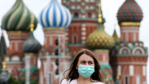 Långhårig kvinna bär ansiktsskydd framför ortodoxa kyrkkupoler.