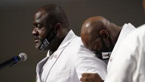 En man håller tal och en annan lutar huvudet mot hans axel.