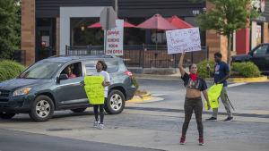 Två kvinnor med varsin skylt med slogans mot polisbrutalitet står utanför en restaurang och protesterar.