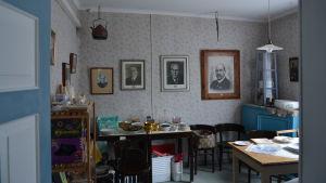 Ett rum med tavlor på några av Finlands presidenter på väggarna. På flera bord i rummet finns lösöre som är till salu på loppis.
