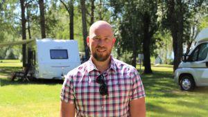 Man i rutig skjorta ler mot kameran. I bakgrunden syns husvagnar.