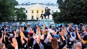 Mielenosoittajien joukko seisoo mellakkavarusteissa olevan poliisiketjun edessä ja pitää käsiään ylhäällä. Taustalla näkyy Valkoinen talo ja Andrew Jacksonin patsas.