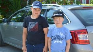 Två pojkar står framför sin gråa bil.