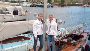 Catharina Sandman och Cecilia Sandman står vid masten på deras tävlingssegelbåt.