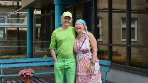 Ett par med färggranna kläder som står framför en gammal sjukhusbyggnad.