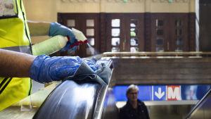 En städare, vars händer endast syns, desinficerar ledstången på en rulltrappa vid Helsingfors Järnvägsstation.